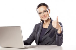 Smiling business woman showing thumbs up next to her laptop